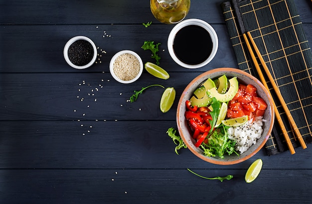 Hawaiian lachs fisch poke bowl mit reis, avocado, paprika, sesam und limette. Premium Fotos