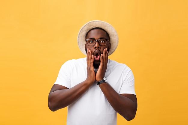 Headshot des doof überraschten jungen mannes mit dunkler hautfarbe, der ein zufälliges weißes t-shirt trägt, starrt die kamera mit entsetztem blick an. Premium Fotos
