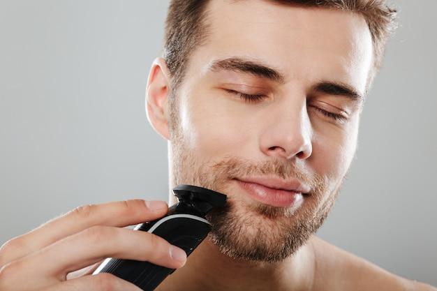 Headshot des kaukasischen erfreuten kerls 30s, der am badezimmer beim rasieren des gesichtes mit trimmer über grauer wand ausgezogen wird Kostenlose Fotos