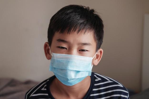 Headshot-porträt des kranken jugendlichen jugendlichen asiatischen jungen, der eine maske trägt Premium Fotos