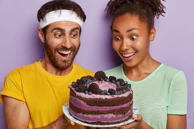 Headshot von glücklichen frauen und männern, die froh und überrascht sind, die erlaubnis des fitnesstrainers zu erhalten, leckeren kuchen zu essen Kostenlose Fotos