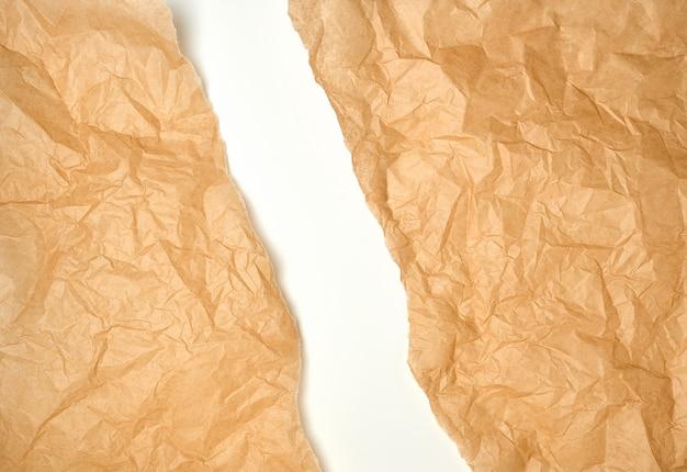 Heftiges zerknittertes braunes pergamentpapier, weißer hintergrund Premium Fotos