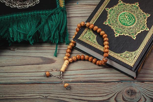 Heiliger koran mit perlen über holzoberfläche Premium Fotos
