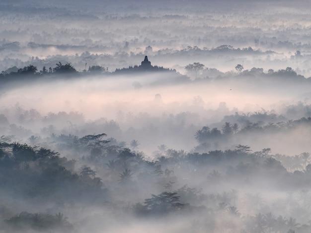 Heiliger tempel von borobudur in einem schönen nebligen sonnenaufgang vom setumbu hill aus gesehen Premium Fotos
