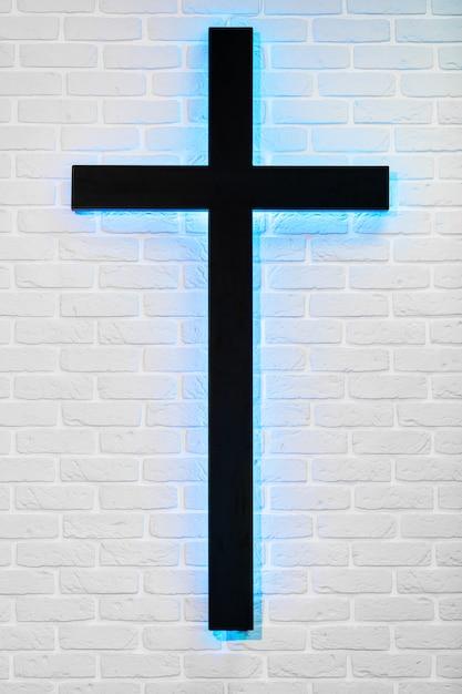 Heiliges kreuz auf seite der weißen backsteinmauer Premium Fotos
