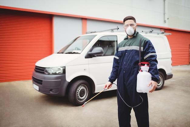 Heimwerker mit dem insektizid, das vor seinem packwagen steht Premium Fotos
