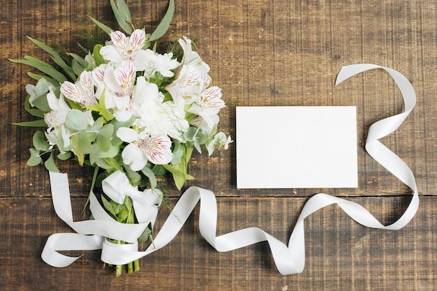 Heiratender blumenstrauß der weißen karte und der peruanischen lilie gebunden mit band auf hölzernem schreibtisch Kostenlose Fotos