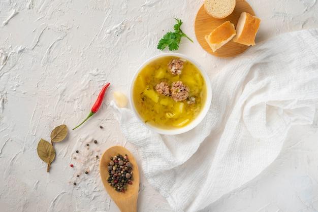 Heiße frische gekochte suppe mit fleischklöschen und kartoffel mit brot auf einer weißen tabelle, geschmackvolle abendessen Premium Fotos