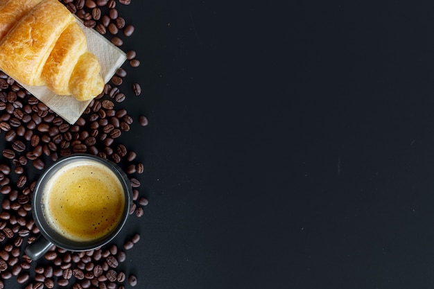 Heiße kaffee-, bohnen- und butterhörnchen auf schwarzer tabelle Premium Fotos