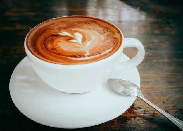 Heiße kaffee lattekunst auf hölzernem tabellenhintergrundabschluß oben Premium Fotos