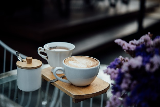 Heiße lattekunst in der kaffeetasse auf hölzerner tabelle in der kaffeestube Kostenlose Fotos