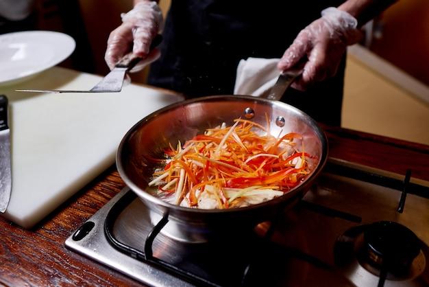 Heiße pfanne mit fleisch und gemüse auf dem herd. ein koch bereitet teller auf küche des restaurants zu. Premium Fotos