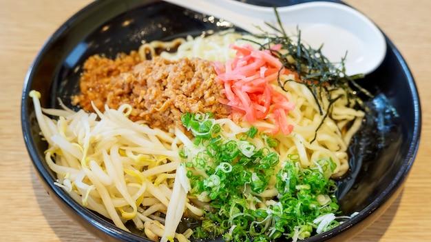 Heiße ramennudel (japanisches lebensmittel) in einer schwarzen schüssel, weichzeichnung. Premium Fotos