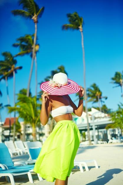 Heiße schönheit im bunten sunhat und im kleid gehend nahe strandozean am heißen sommertag auf weißem sand Kostenlose Fotos