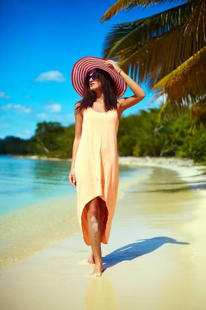 Heiße schönheit im bunten sunhat und im kleid gehend nahe strandozean am heißen sommertag nahe palme Kostenlose Fotos