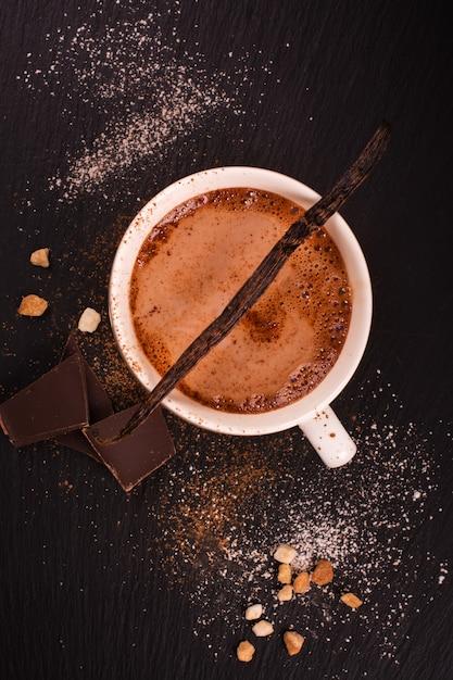 Heiße schokolade in der weißen porzellanschale über schwarzem steinhintergrund Premium Fotos