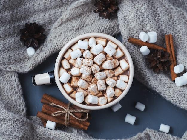 Heiße schokolade oder kakao mit marshmallows in einer zimtschale. warmer strickschal Premium Fotos