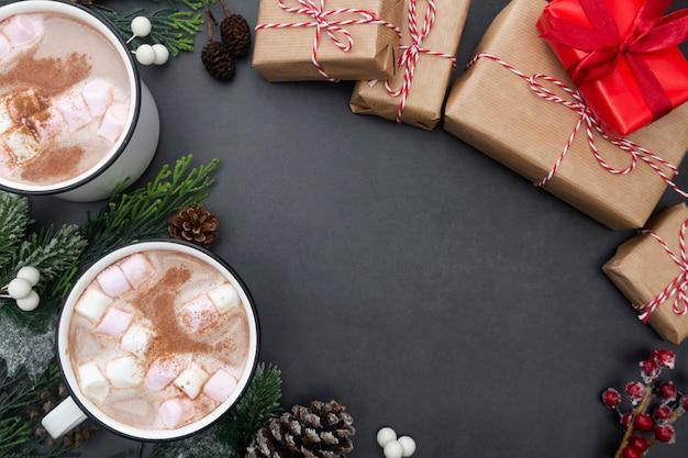 Heiße schokoladenbecher mit eibischen und weihnachtsgeschenkboxen. Premium Fotos