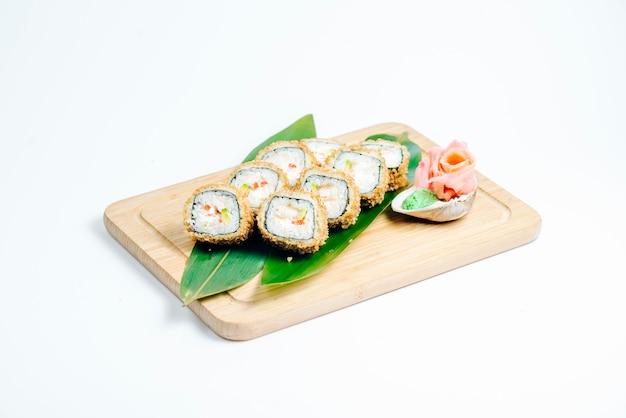 Heiße sushirollen mit tempura und avocado dienten auf blättern auf hölzernem brett Kostenlose Fotos