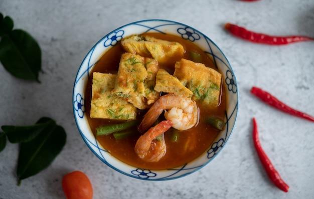 Heiße und saure suppe mit cha-om, ei und garnelen in einer weißen schüssel mit chili-kaffir-limettenblättern auf weißer oberfläche. Kostenlose Fotos