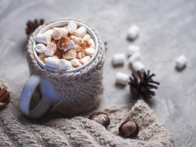 Heiße wintergetränkschokolade, -kakao oder -kaffee mit eibischen auf dem tisch in einer gestrickten tasse mit zimt Premium Fotos