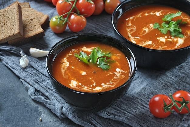Heiße wintersuppe. glühende tomatensuppe mit knoblauch, süßem paprika, petersilie, serviert mit sahne und sauerteigbrot in zwei schwarzen keramikschalen auf grauem hintergrund Premium Fotos