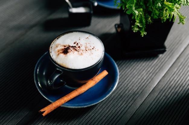 Heißer cappuccino mit zimt diente in der blauen schale. Premium Fotos