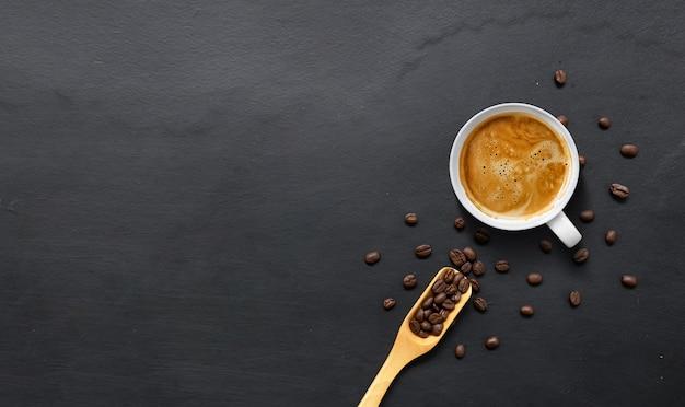 Heißer espresso und kaffeebohnen auf schwarzem holztischhintergrund. draufsicht Premium Fotos