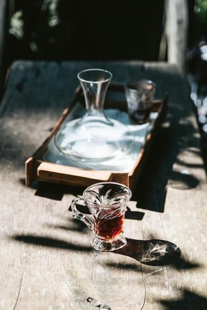Heißer filterkaffee im trinkglas auf holztisch mit hartem sonnenlicht. Premium Fotos