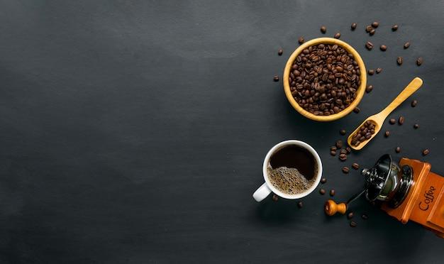 Heißer kaffee, bohne und handmühle auf schwarzem tischhintergrund. platz für text. draufsicht Premium Fotos