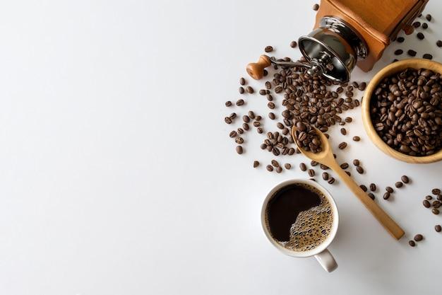 Heißer kaffee, bohne und handmühle auf weißem tischhintergrund. platz für text. draufsicht Premium Fotos