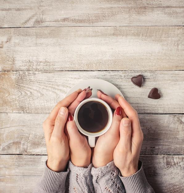 Heißer kaffee in den händen eines geliebten menschen. Premium Fotos