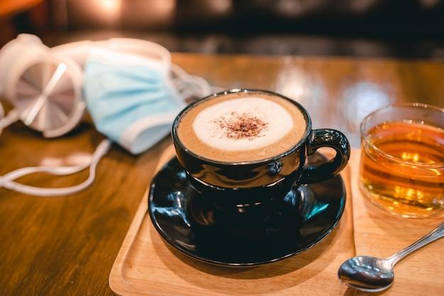 Heißer kaffee in einer schwarzen tasse und 1 tasse tee, der zusammen im café während des corona-virus oder covid-19 serviert wird Premium Fotos