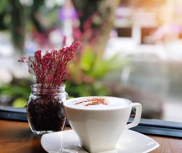 Heißer kaffee in einer weißen schale auf holztisch- und blumenvase im kaffeestubeunschärfehintergrund Premium Fotos
