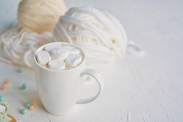 Heißer kaffee mit eibisch in einem weißen becher neben zitronen- und erdbeerschokolade Premium Fotos