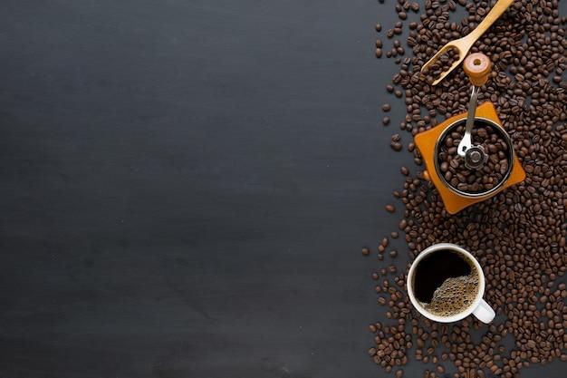 Heißer kaffee und bohne auf schwarzem holztischhintergrund. draufsicht Premium Fotos