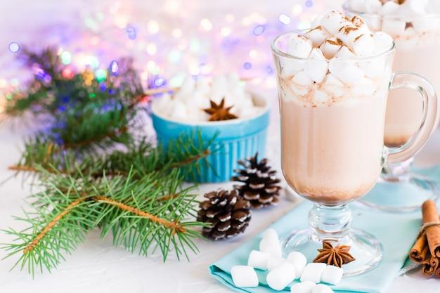 Heißer kakao mit eibisch und gemahlenem zimt in gläsern in den weihnachtsdekorationen Premium Fotos
