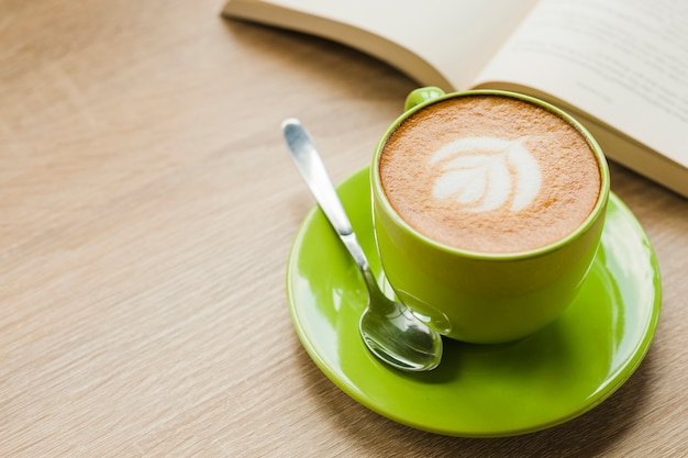 Heißer lattekaffee mit lattekunst in der grünen schale auf tabelle Kostenlose Fotos