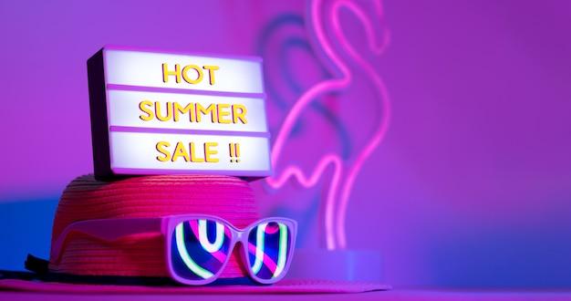 Heißer sommerschlussverkauf im leuchtkasten auf hut mit sonnenbrille rosa und blaues und grünes neonlicht auf tabelle Premium Fotos