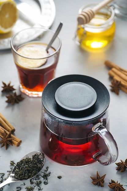 Heißer tee in einer glasteekanne auf einem steingrauen hintergrund Premium Fotos