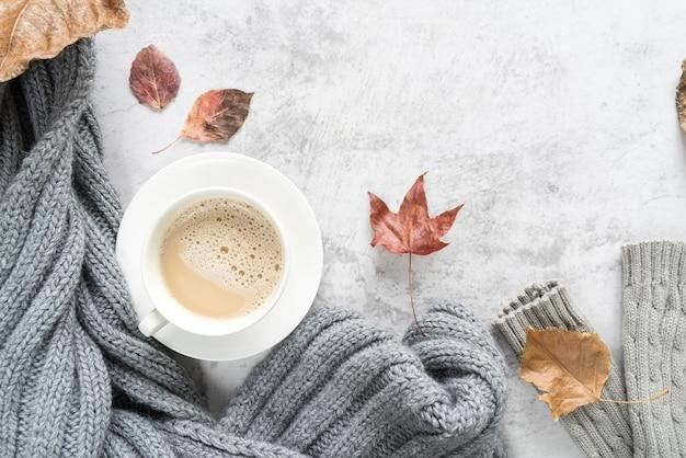Heißes getränk mit warmer strickjacke auf heller oberfläche Kostenlose Fotos