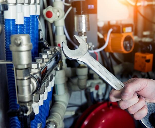 Heizungsingenieur repariert modernes heizsystem im heizraum. automatische steuereinheit. Premium Fotos