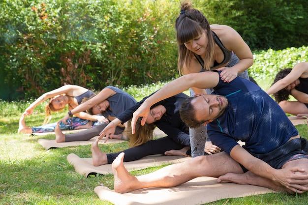 Helfender auszubildender des weiblichen yogalehrers Kostenlose Fotos