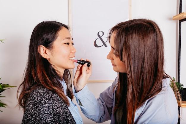 Helfender Freund des Mädchens mit Make-up Kostenlose Fotos