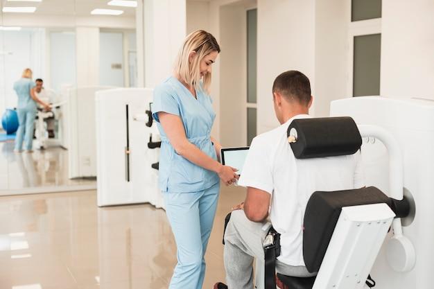 Helfender patient hinteren ansichtdoktors mit einem medizinischen trainiert Kostenlose Fotos
