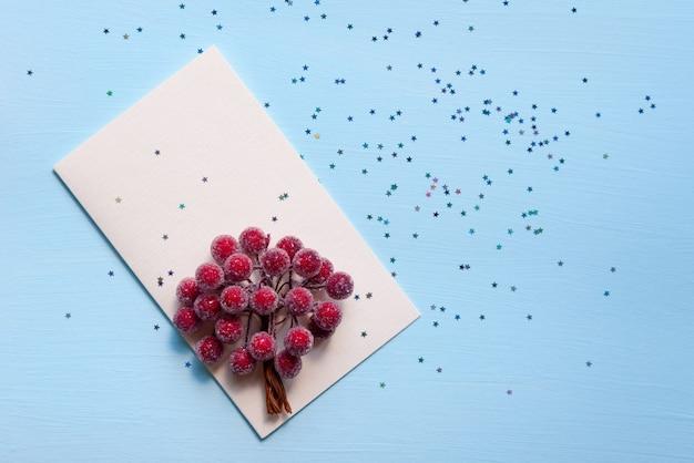 Hellbeige karten auf blauem grund mit glänzenden sternen und zierbeeren. dekoration für weihnachten und neujahr. Premium Fotos