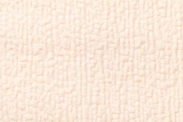Hellbeiger flauschiger hintergrund aus weichem, flauschigem stoff Premium Fotos