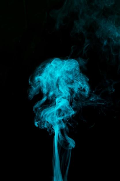 Hellblauer rauch, der gegen schwarzen hintergrund durchbrennt Kostenlose Fotos