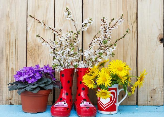Helle blumen in töpfen, rote gummistiefel auf einem hölzernen hintergrund. frühlingsblumenstillleben. valentinstag Premium Fotos