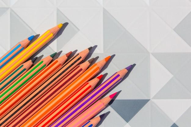 Helle farbbleistifte auf modernem niedrigem poly, geometrisches abstraktes design des polygons. Premium Fotos
